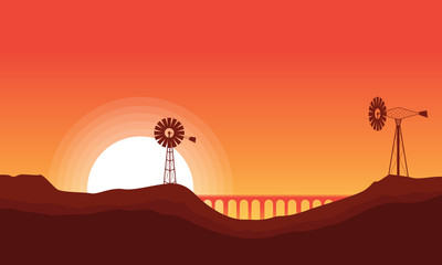 Silhouette of windmill and bridge