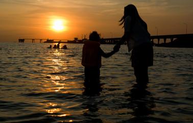 People walk ocean beach sunset