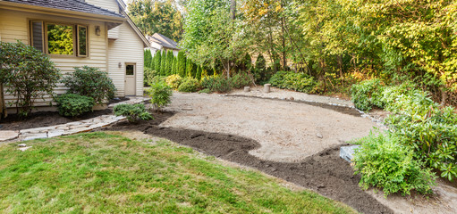 Fotobehang - Patio area marked out with topsoil placed on flower bed areas and stone retaining wall built around the far edge