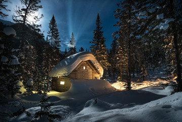 Small cottage in a beautiful snow forest at moon night