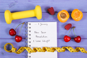 New year resolutions written in notebook on purple board