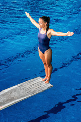 Wall Mural - Female diver. Female diver standing on the jumping board.