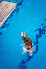 Wall Mural - Diver;s jump. Female diver jumping into the pool
