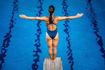 Wall Mural - Female diver standing on the jumping board.