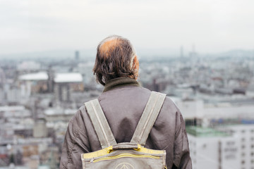 Back of an Old man looking at the city scape in Kyoto, Japan