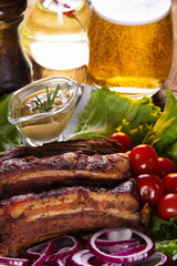 Baked pork ribs with vegetables, mustard and a glass of beer on a wooden table