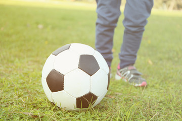 Close up view of boy's legs and ball on green grass
