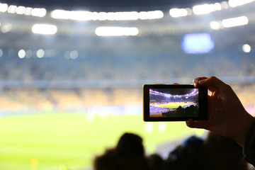 Fan taking video of football game at stadium