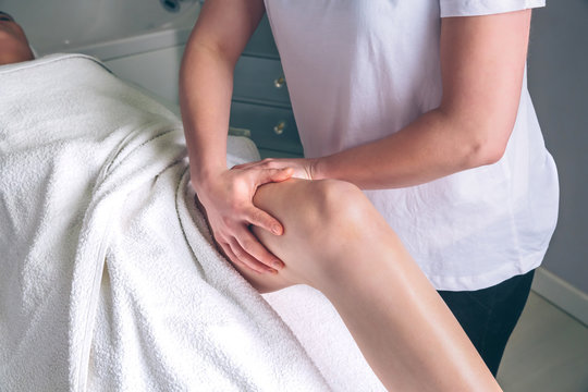 Close up of female therapist hands doing lymphatic drainage massage on legs of woman in a clinical center. Medicine, healthcare and beauty concept.