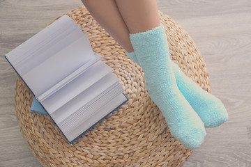 Human legs in knitted socks on ottoman beside open book