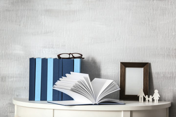 Books with frame on the table, on gray wall background