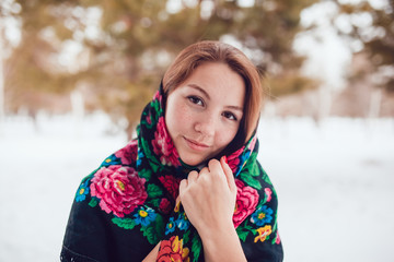 Russian beauty woman with red hair and freckles in the national scarf stands on a background of trees.