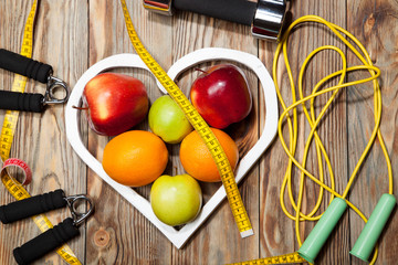 White heart, apples and oranges, healthy diet, dumbbells  a jump rope on  wooden background