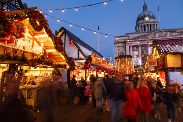 Families enjoying Nottingham Christmas Market in the evening.