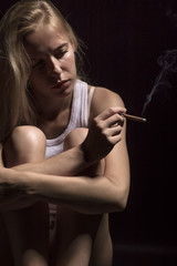young woman sitting in dark smoking cigarette