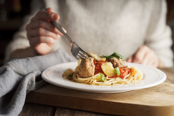 Woman eating spaghetti with meatballs