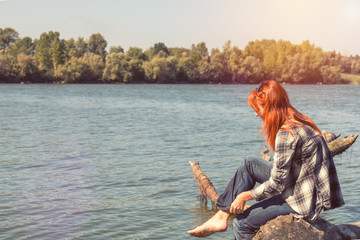 Young woman with red hair in checkered shirt and sunglasses at the river in the sunny day. Coloring and processing photo with soft focus in instagram style.
