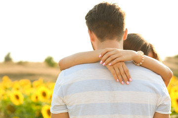 Young man standing back and girl hugging his neck