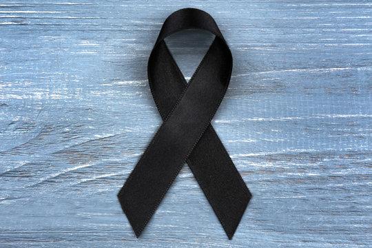 Black ribbon on grey wooden background. Melanoma and mourning concept