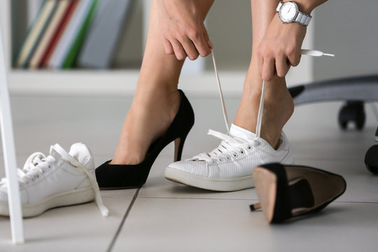 Woman changing shoes in office at work