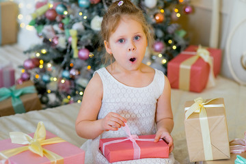Happy blonde girl with Christmas gifts