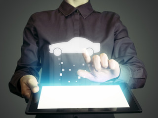 Image of a girl with tablet in her hands. She looking for a car for buying or for rent, using online searching service.