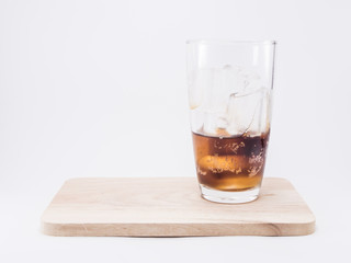 one of thirds soft drink is cool with  two of thirds ice cubes in glass on wood squares