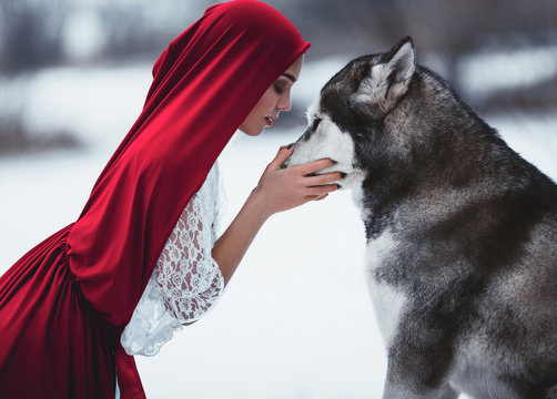 Girl in costume Little Red Riding Hood with dog malamute like a