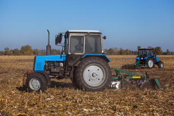 Two big blue tractor plowing a field and remove the remains of previously mown corn. The work of agricultural machinery. Harvest