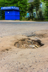 The hole in the asphalt on the road in the village.
