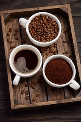 Different types of coffee - ground, grain and beverage on dark wooden background, selective focus, vertical.