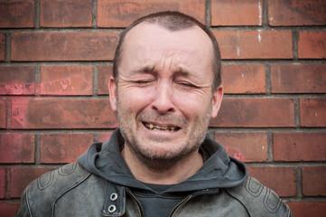 homme entrain de pleurer de dan un mur de briques,