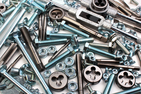 Many shiny bolts with nuts, taps and dies on white background