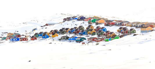 Colorful cabins on the hill covered in snow, Aasiaat city, Green