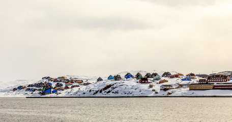 Colorful cabins on the hill covered in snow, Aasiaat city panora