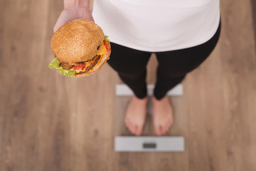 Diet And Fast Food Concept. Overweight Woman Standing On Weighin