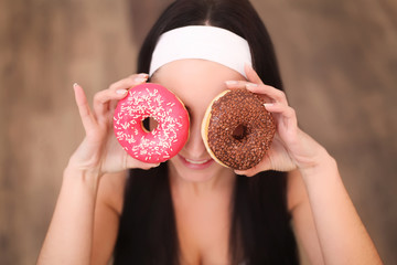 Beauty fashion model girl taking sweets and colorful donuts. Funny joyful styled woman with sweets on wood background. Diet, dieting concept. Junk food, Slimming, weight loss