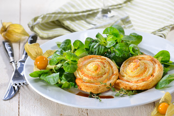 Herzhafte Blätterteig-Lachsschnecken mit Frischkäse und Kräutern auf Feldsalat - Baked hearty puff pastry snacks with smoked salmon, cream cheese and fresh herbs on lambs lettuce