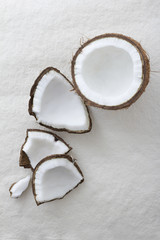 Pieces of a whole coconut cracked open on a textured white background and viewed from above