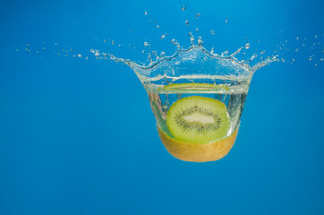 Kiwi splashing in water with blue background
