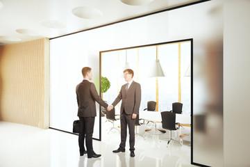 Businessmen shaking hands in interior
