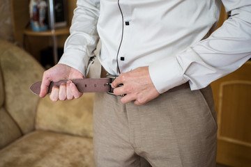 Man buttons belt. Men's style. Professions. To prepare for work,
