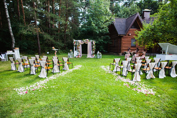 Beautiful wedding ceremony outdoors. Decorated chairs stand on the grass. Wedding arch made of cloth and white and pink flowers on a green natural background. Old doors, rustic style.