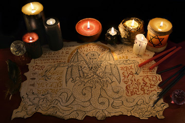 Black magic ritual with demon manuscript and evil candles