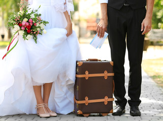 Groom and bride with vintage suitcase on path in park