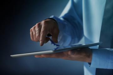 Businessman touching screen of modern tablet, closeup