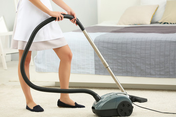 Chambermaid cleaning room with vacuum cleaner