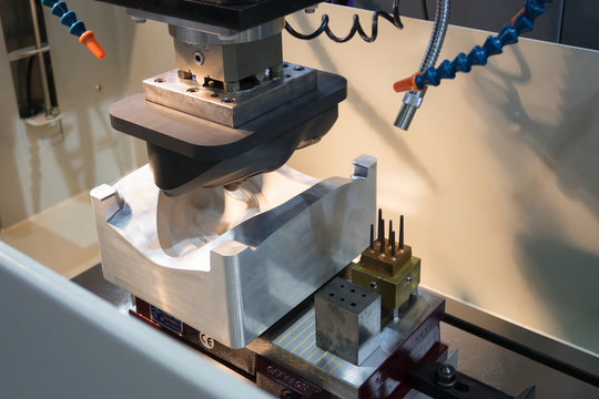EDM Industrial machine working with coolant injection in the factory. Close up at Industrial machine.