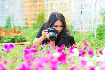 Nature female Photographer taking pictures outdoors in flower garden