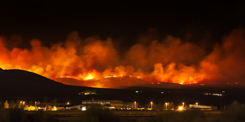 Wildfire burning at night in Northern Nevada with smoke and flames